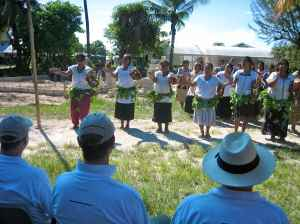 The AMAK women perform a traditional garlanding ceremony in front of Mark, Paul and John.