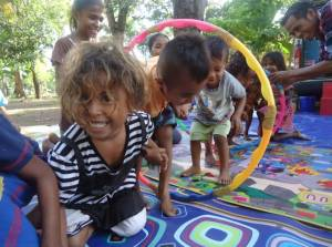 Community children play with the hula hoop tunnel after reading.