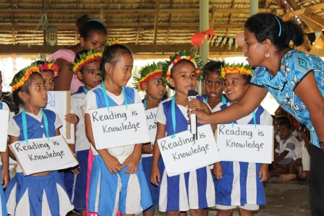 """Pre-School children from Buota village presenting their rhyme relating to the library day theme """"reading is knowledge""""."""