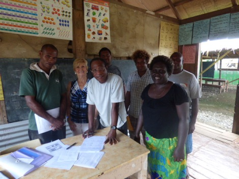 Chairman Dickson Koke signing the MAMA funding agreement. He is surrounded by fellow board members and building supervisor (L-R: James Qwauna, Joyce Boykin, Dickson Koke, Fred Kinata, Patteson Amos (Builder), Grace Rifasia and Hamuel Abeta)