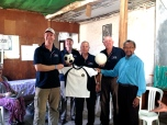 Paul Singer, Mark Fraser, Phil Singer and John Fraser handing over the sporting equipment to Father Tiago which was donated by the Gungahlin United Football Club.